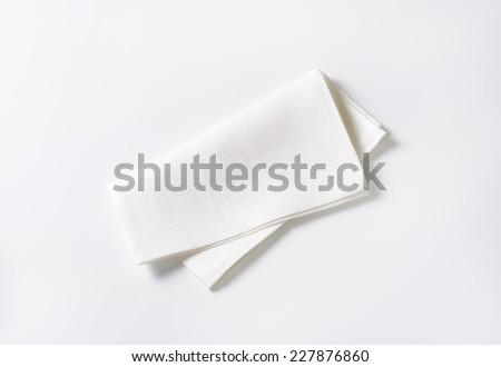 folded white napkin on white background - stock photo