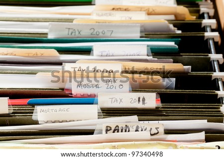 Folders in file drawer sorted into tax years and mortgage documents - stock photo