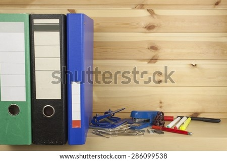 Folders, staplers and hole punches lying on a shelf in the office. - stock photo