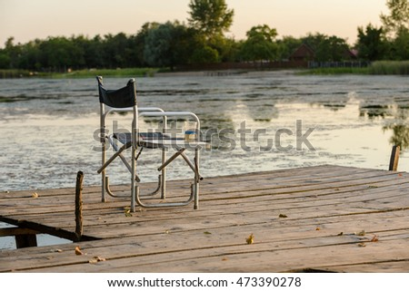 Folding chair on the pier at sunset