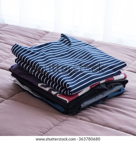 Folding clothes on the bed before keeping in wardrobe - stock photo