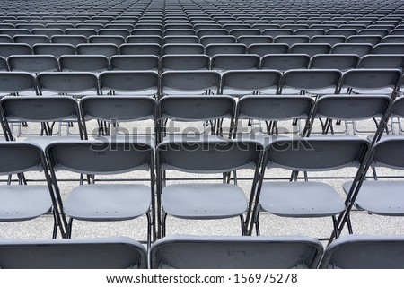 Folding plastic chairs for outdoor music concert - stock photo