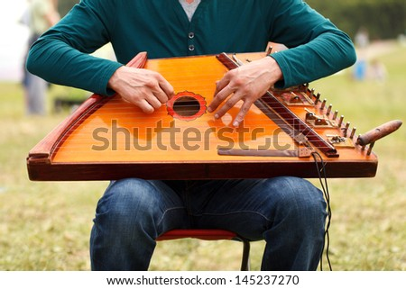 Folk musician playing gusli at Moscow Historical Festival Times and Epoch in Kolomenskoe - stock photo