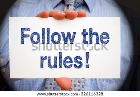 Follow the rules - Businessman holding sign with text - stock photo