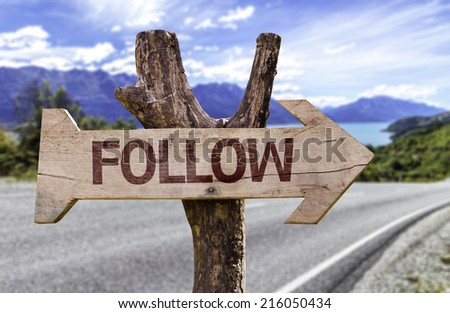 Follow wooden sign with a road background - stock photo
