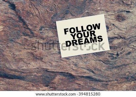 Follow your dreams text on white paper on wood background