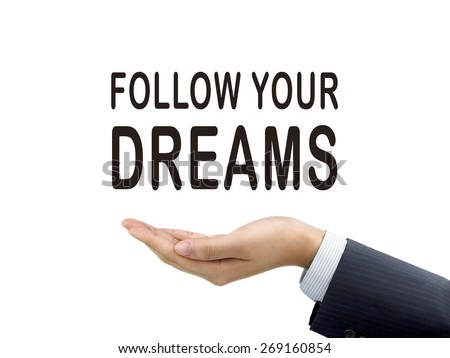 follow your dreams words holding by businessman's hand over white background - stock photo