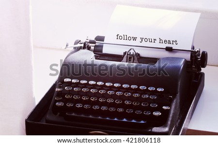 Follow your heart message on a white background against typewriter on a table - stock photo