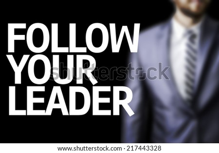 Follow your Leader written on a board with a business man on background - stock photo