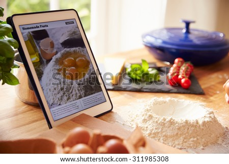 Following Pasta Recipe Using App On Digital Tablet - stock photo