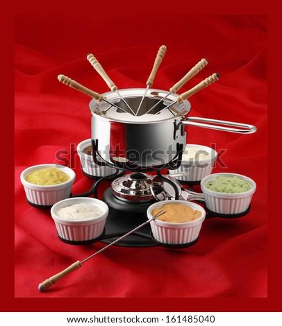 fondue on red fabric background - stock photo