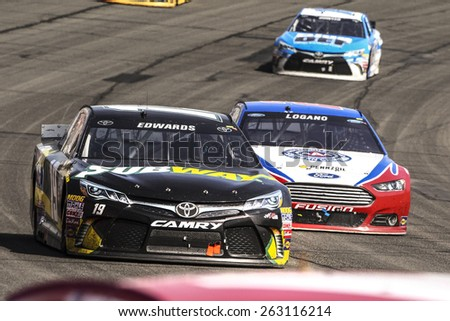 Fontana, CA - Mar 22, 2015:  Carl Edwards (19) brings his race car through the turns during the  race at the Auto Club Speedway in Fontana, CA. - stock photo