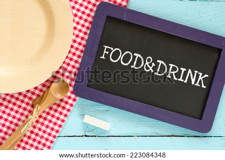 Food & Drink. Chalkboard with wooden spoon and plate on a red checkered tablecloth and text Food & Drink - stock photo