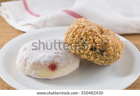 Food and Bakery, Two Delicious Sweet Donuts with Strawberry Jam, Chocolate and Peanuts Toppings - stock photo