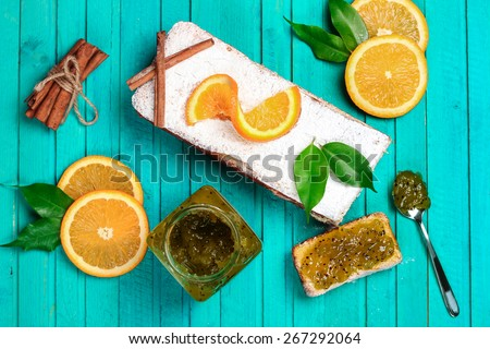Food and drink, still life concept. Home made orange cake with kiwi confiture on a wooden table. Selective focus, top view - stock photo