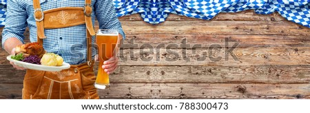 Food and drinks are served by waiter wearing traditional Bavarian leather trousers