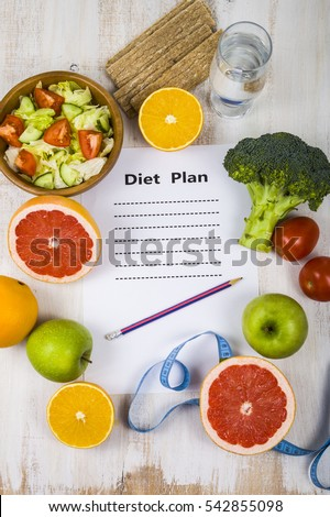 Food and sheet of paper with a diet plan on a  wooden table. Concept of diet and healthy lifestyle.
