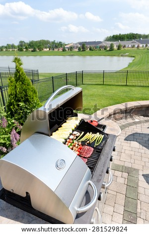 Food arranged ready for grilling on an outdoor gas barbecue in a summer kitchen on a brick paved outdoor patio with a view of a lake in a healthy lifestyle concept - stock photo