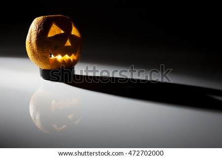 Food art creative concept. Halloween scary face carved into an orange fruit with back light over a dark background.