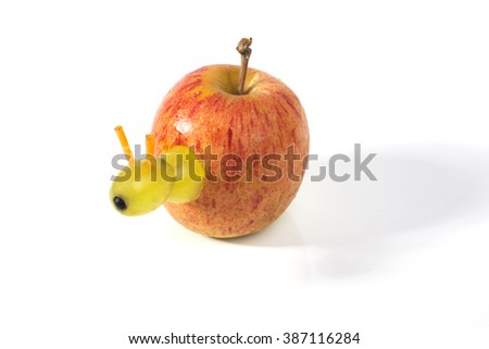 Food art creative concepts. A little worm made of green grapes and carrots is coming out of an apple on white background.
