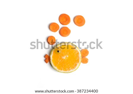 Food art creative concepts. Cute round fish made of fruits, orange, grapes and carrots. - stock photo