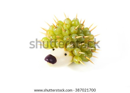 Food art creative concepts. Funny and cute hedgehog made of pear, green grapes and olive nose isolated on a white background. - stock photo