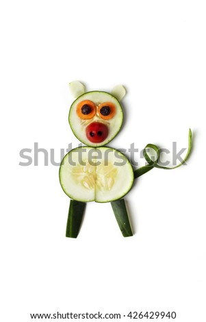 Food art creative concepts. Funny and cute pig made of cucumber, carrots, tomato and raisins isolated on a white background. - stock photo