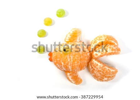 Food art creative concepts. Very cute gold fish made of tangerine orange fruit, grapes and carrots. - stock photo