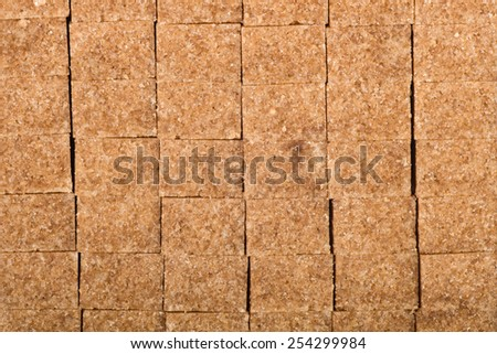 Food background: Brown cane sugar cubes - stock photo