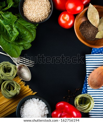 Food background, fresh vegetables, tomatoes, peppers, green spinach, salt, rice, pasta, spices and kitchen utensils on a black background, close-up - stock photo