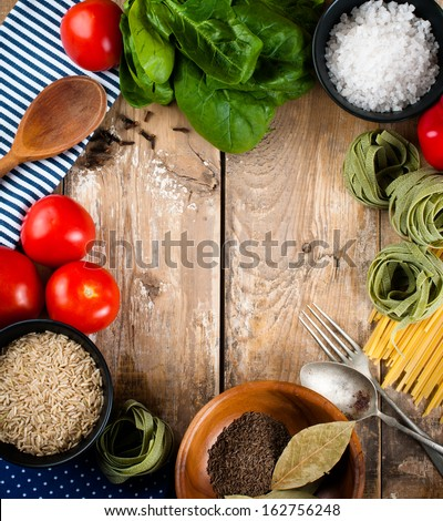 Food background, fresh vegetables, tomatoes, peppers, green spinach, salt, rice, pasta, spices and kitchen utensils on a wooden board, close-up