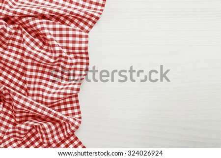 Food background, high angle view of white wooden table and folded, checkered tablecloth white copy space - stock photo