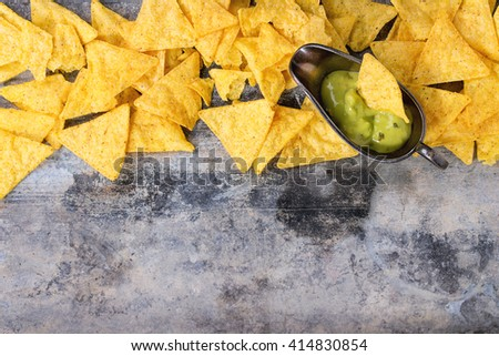 Food background. Mexican nachos chips with guacomole sauce over old textured tin background. Top view. With space for text