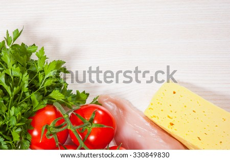 Food background of fresh chicken breast, cheese and tomato at the wooden board with copy space