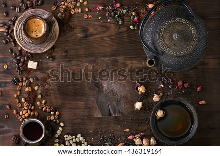 Food background tea and coffee theme. Different black and green dry tea, different coffee beans, cup of hot tea and coffee,  teapot over dark wooden background. Top view. Space for text