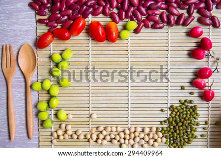 Food background texture decorated with beans and fresh organic foods on wooden table - stock photo