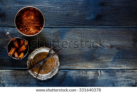 Food background with cocoa powder, vanilla and cinnamon sticks over dark wood. Christmas and holidays concept. Copy space. Top view. - stock photo