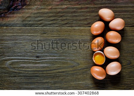 Food background with eggs and one yolk over rustic texture. Top view. Space for text. - stock photo