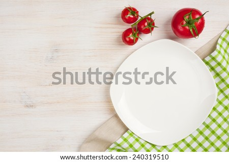 Food background with empty plate, tomatos and kitchen towel - stock photo