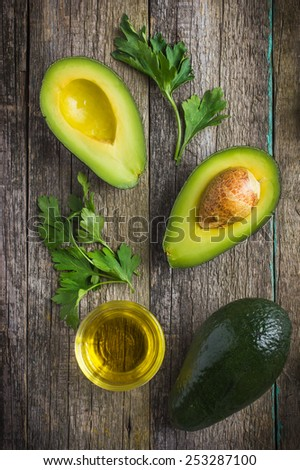 food background with fresh organic avocado, lime, parsley and olive oil on  old wooden table, top view - stock photo