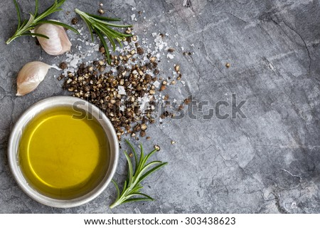 Food background with olive oil, peppercorns, sea salt, rosemary, and garlic cloves, over dark slate background.  Overhead view.