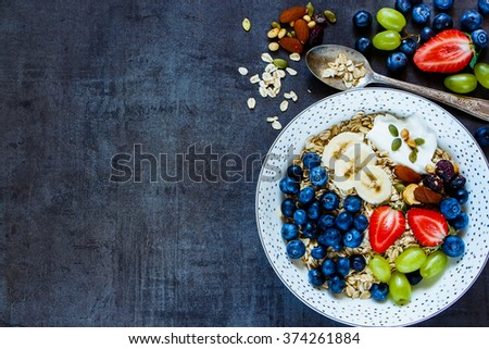 Food background with plate of oat flakes, berries with yogurt and seeds for tasty breakfast on dark vintage board -  Diet, Detox, Clean Eating or Vegetarian concept. - stock photo