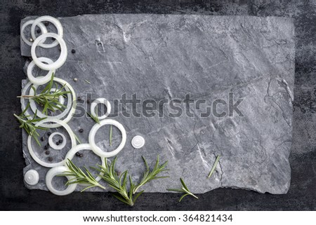 Food background with sliced onions, peppercorns and rosemary on gray slate.  Overhead view. - stock photo