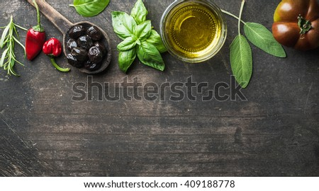 Food background with vegetables, herbs and condiment. Greek black olives, fresh basil, sage, rosemary, tomato, peppers, oil on dark rustic wooden background. Top view, copy space - stock photo