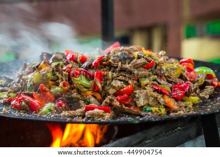 Food Beef bbq on grill with fire served with tomatoes and roast vegetables - stock photo