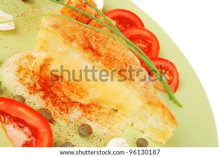 food : cheese casserole piece over green plate served with chives and tomatoes isolated over white