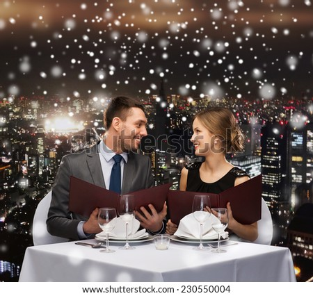 food, christmas, holidays and people concept - smiling couple with menus at restaurant over snowy night city background