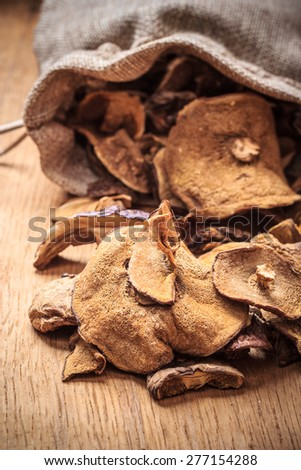 Food. Closeup dry mushrooms spilling out from burlap sack on wooden surface table background. - stock photo