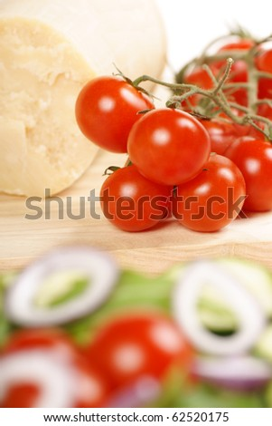 Food composition with ripe cherry tomatoes and parmesan cheese on a wooden cutting board. In the foreground a mixed salad. Selective focus on the background. Shallow DOF - stock photo