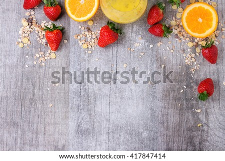 Food concept background with ingredients for healthy breakfast. Muesli flakes, mango smoothie with chie seeds, sliced orange and strawberries on white wooden background. Flat lay. Copy space - stock photo